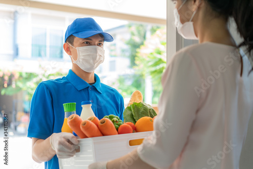 Asian delivery man wearing face mask and glove with groceries box of food, fruit, vegetable and drink give to woman costumer in front of the house during time of home isolation.