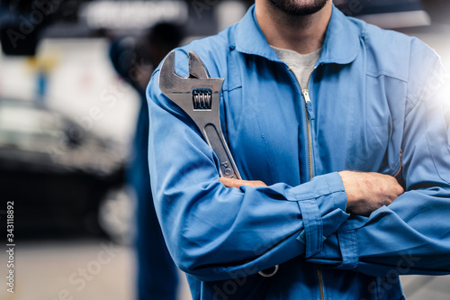 Leinwand Poster No face shot of car mechanic male worker holding equipment tool standing in maintenance and repair automotive garage shop