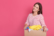 Leinwandbild Motiv Image of brunette lady with pleasant appearance, standing with box in hands against pink wall, doing charity work, poses with clothes for poor and homeless people. Copy space for advertisement.