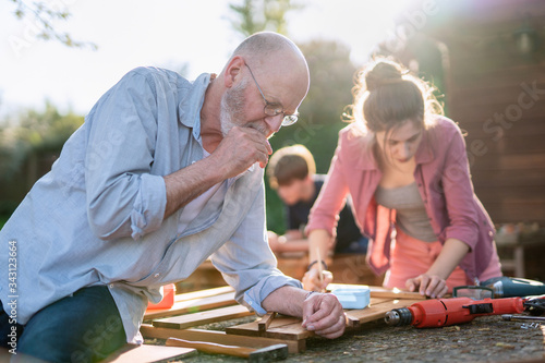 Fototapeta A man and his family are building wooden planters for their vegetable garden obraz