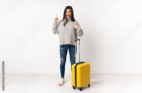 A full length body of a traveler woman with a suitcase over isolated white wall Canvas Print