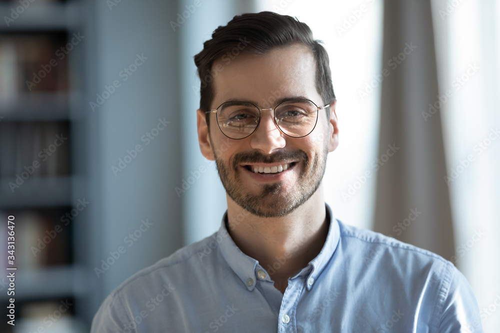 Fototapeta Head shot portrait close up smiling confident businessman wearing glasses looking at camera, standing in modern cabinet, successful happy young man, employee, worker in eyewear posing for photo