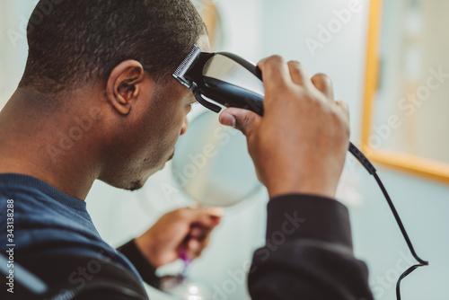 Photo Personal hygiene, african american man cutting his own hair in the bathroom