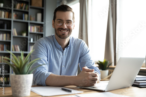 Foto Head shot portrait smiling businessman wearing glasses sitting at work desk with