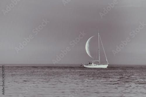 Naklejka premium Optical Illusion Of Sailboat Sailing On Sea Against Half Moon