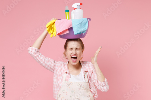 Obraz Crazy woman housewife in apron doing housework isolated on pink background. Housekeeping concept. Hold basin with detergent bottles washing cleansers on head keeping eyes closed spreading hand scream. - fototapety do salonu