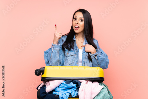 Traveler Colombian girl with a suitcase full of clothes over isolated pink backg Canvas Print