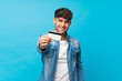 canvas print picture - Young handsome man over isolated blue background holding a credit card