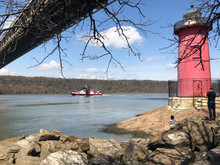 New York, USA. April 2020. New York Fire Department Boat Underway On River Hudson Under George Washington Bridge From The Little Red Lighthouse. Jeffrey's Hook Light.