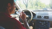 Man Sipping Drink While Drivin...