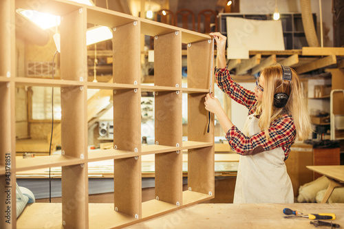 Obraz confident beautiful woman work as carpenter in workshop, young lady use tape-line, measures distance between shelves - fototapety do salonu