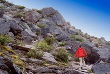 Low Angle View Of Man Climbing Rocky Mountain