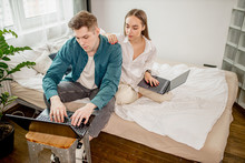 Young Caucasian Married Couple Work Together At Home Using Laptop, Man And Woman Do Their Own Business At Freelance. Home, Work, Freelance Concept. Everyone Sit At Home During Quarantine