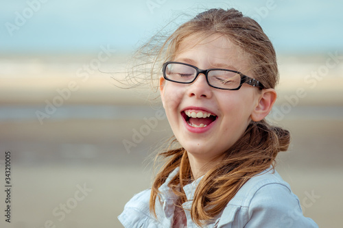 Portrait of a windswept girl outside laughing hard with eyes closed and glasses Slika na platnu