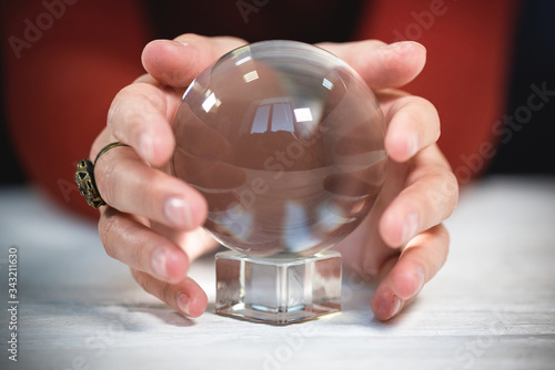 Photo Future reader is holding her hands around the crystal ball close up