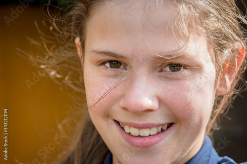 A portrait of a fresh-faced teenage girl, smiling in a natural windswept sunny e Fototapeta