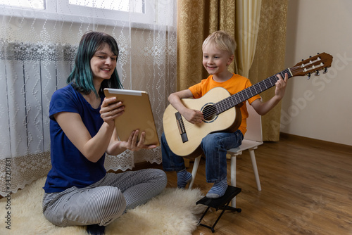 Fotografia Cute boy plays the guitar, mom holds a tablet and shows to his son and smiles