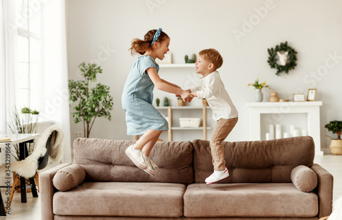 Obraz na plátně Happy siblings jumping on sofa.