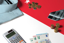 Singapore Flag On Minimal Money Concept Table. Coins And Financial Objects On Flag Surface. National Economy Theme.