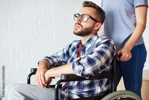 Obraz Woman helping disabled man in wheelchair - fototapety do salonu