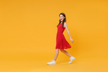 Side View Of Cheerful Young Brunette Woman Girl In Red Summer Dress Posing Isolated On Yellow Background Studio Portrait. People Sincere Emotions Lifestyle Concept. Mock Up Copy Space. Looking Camera.