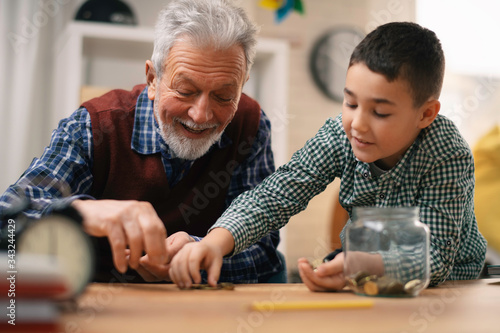 Fotografía Grandpa and grandson saving money