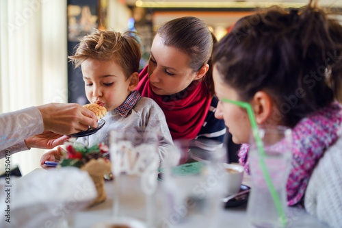 Photo Small little boy three years old child son is sitting in the lap of his mother o