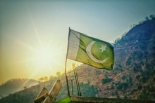 Low Angle View Of Pakistani Flag Against Sky During Sunset