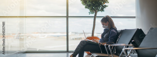 Fotografiet A woman is sitting at the airport with a laptop in a medical mask