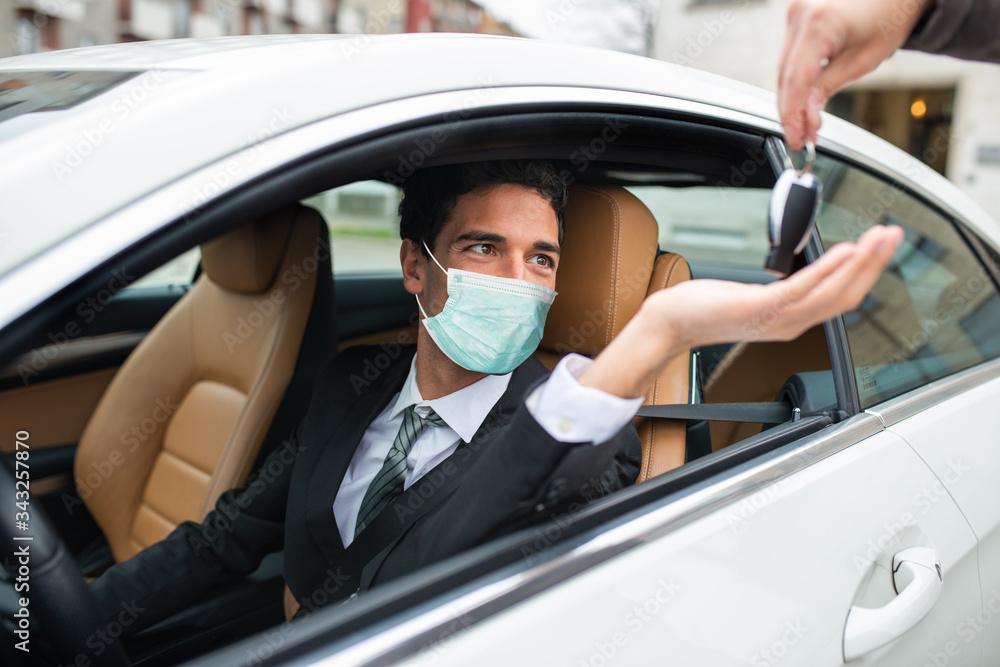 Obraz Masked man taking the car keys fototapeta, plakat