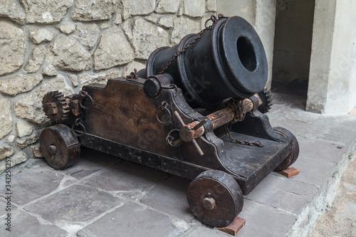 Fototapeta Old cannon over stone wall