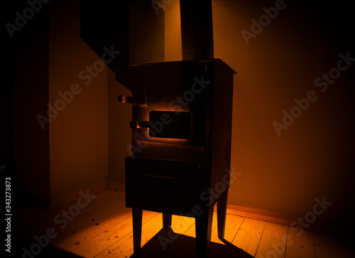 Obraz Fire burning in small black iron stove. Closeup photo with selective focus - fototapety do salonu