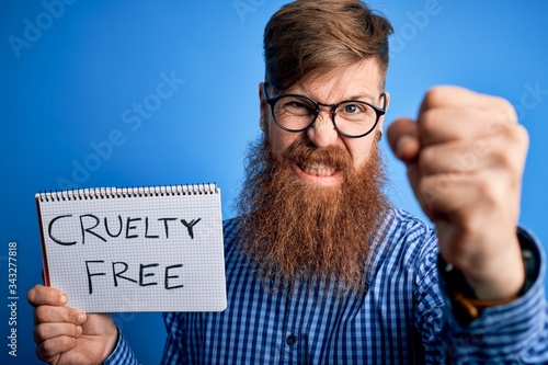 Photo Redhead Irish man with beard holding cruelty free vegan cosmetics message over b