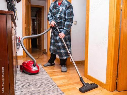 Photo Man vacuuming down hallway of home with hardwood floor during alertness