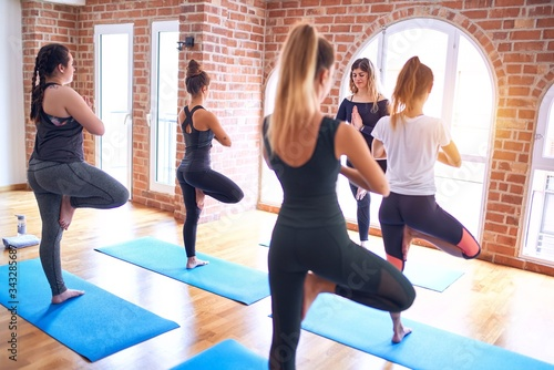 Young beautiful group of sportswomen practicing yoga Canvas