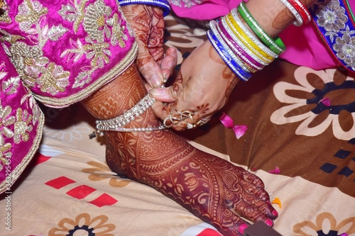 Cropped Hands Of Woman Wearing Anklet To Bride In Wedding Ceremony Canvas Print