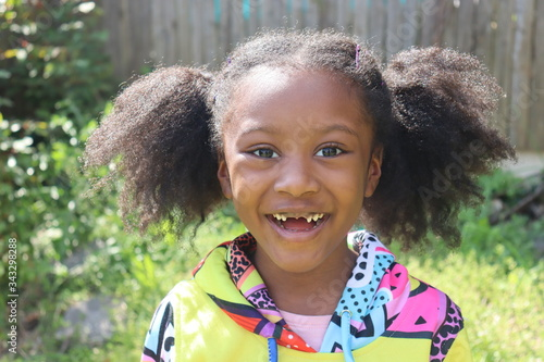 Vászonkép Happy African American girl missing two front teeth outdoors