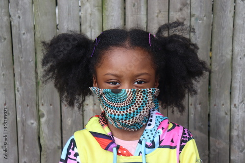 Cute African American Girl with pigtails wearing pattern fabric face mask outsid Canvas Print