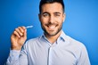 Young handsome man holding dental aligner tooth correction over blue background with a happy face standing and smiling with a confident smile showing teeth