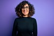 Leinwandbild Motiv Young beautiful curly arab woman wearing casual sweater and glasses over purple background with a happy and cool smile on face. Lucky person.