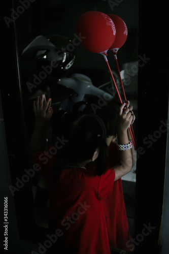 Fotografie, Obraz Rear View Of Girl Holding Balloon In Front Of Mirror With Reflection Of Motor Sc