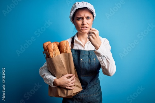 Young beautiful baker woman with blue eyes holding paper bag with  bread annoyed Canvas Print