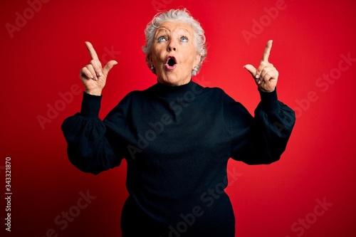 Senior beautiful woman wearing casual sweater standing over isolated red background amazed and surprised looking up and pointing with fingers and raised arms Slika na platnu