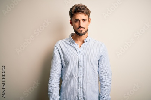 Fotografiet Young handsome man with beard wearing striped shirt standing over white background Relaxed with serious expression on face