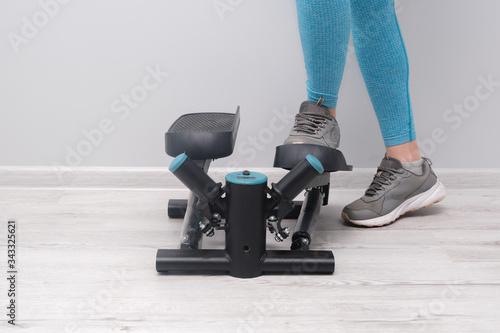 Fotografie, Obraz Woman exercising on a twister  stepper