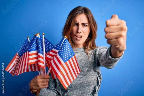 Young beautiful patriotic woman holding united states flags celebrating inepende Canvas Print