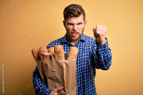 Young blond man with beard and blue eyes holding paper bag with bread annoyed an Canvas Print