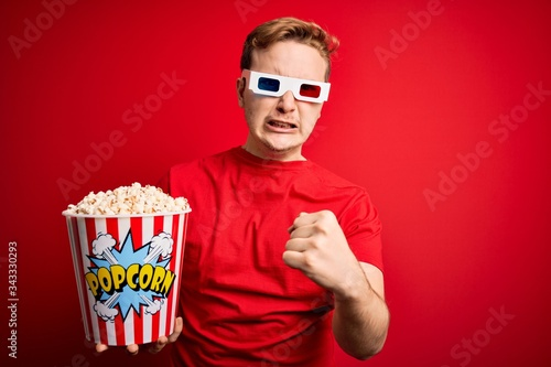 Photo Young handsome redhead man watching 3d glasses eating popcorn snack over red bac