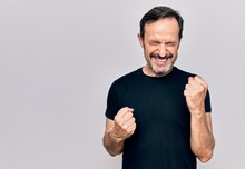 Middle Age Man Wearing Casual Black T-shirt Standing Over Isolated White Background Celebrating Surprised And Amazed For Success With Arms Raised And Eyes Closed