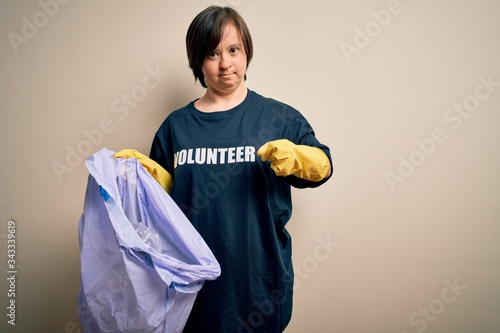 Young down syndrome volunteer woman picking rubbish and plastic from the trash a Canvas Print